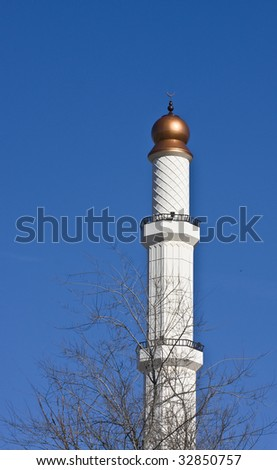 A beautiful tower rising from an Islamic Mosque into the blue sky behind trees in winter