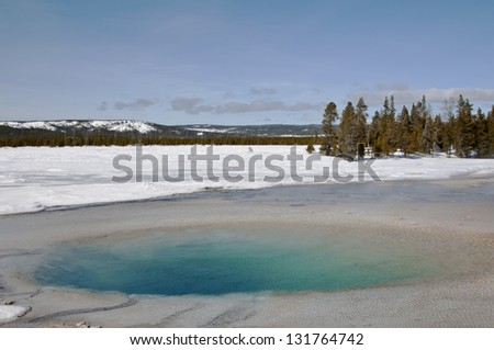 A beautiful turquoise colored pool in the thermal area of Yellowstone National Park in winter. - stock photo