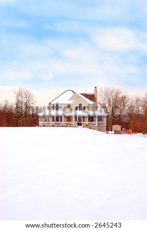 A beautiful two story farmhouse with a wrap around porch sits back from the road on a snow covered hill in winter.