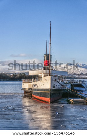 A beautiful view of Loch Lomond in Scotland with a paddle steamboat berthed at Balloch pier. - stock photo