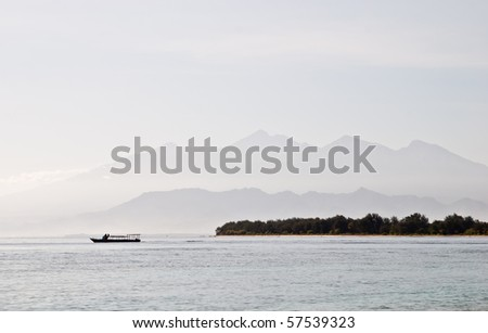 A beautiful view of Mount Rinjani. Silhouette of a boat passing by. Shot from Gili Trawangan