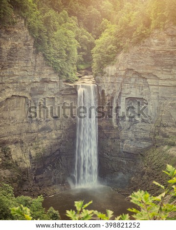 A beautiful view of taughannock falls in Ithaca New York with a waterfall, rock texture and green trees. - stock photo