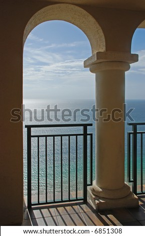 A beautiful view of the ocean through the arches of a balcony. - stock photo