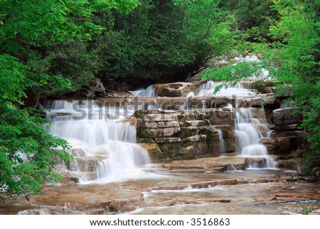 A beautiful waterfall in central New York. Its called Stockbridge falls. Lots of character to this waterfall as it tumbles over colorful rocks. - stock photo