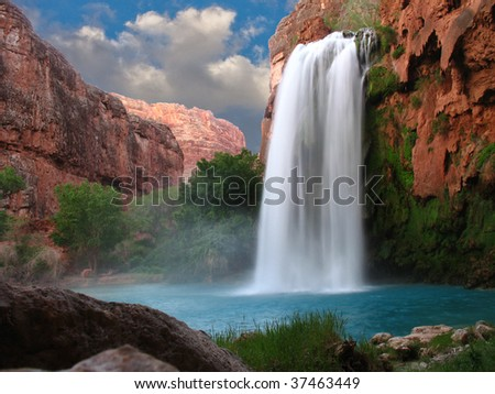 A beautiful waterfall photographed with a slow shutter speed to blur the water - stock photo