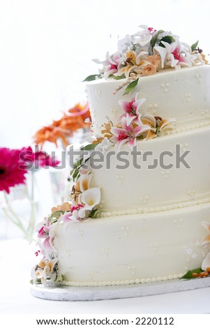 a beautiful wedding cake with a gorgeous candy flower arrangement. This image is heavily back lit with a blown out background - stock photo