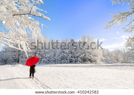 A beautiful winter snow scene with a woman walking with a red umbrella as the snow clings to the trees with a bright blue sky.