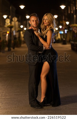 A beautiful woman and handsome man in a city at night - stock photo