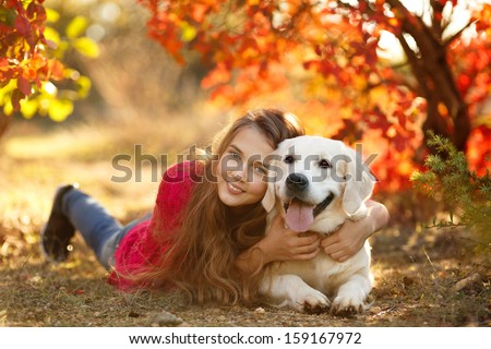 A beautiful woman and her dog (Labrador retriever) posing in autumn park. Red and orange leaves around. - stock photo