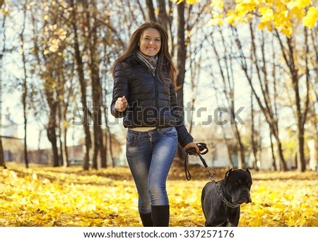 A beautiful woman and his dog Cane corso posing outside in autumn park
