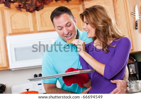 A beautiful woman baking cookies with her husband in the kitchen - stock photo