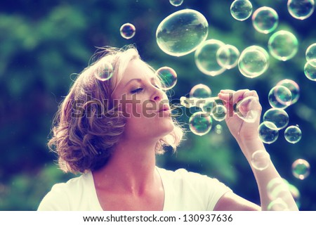 a beautiful woman blowing bubbles toned with a retro vintage instagram filter  - stock photo