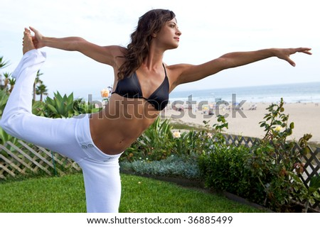 A beautiful woman doing yoga at the beach - stock photo