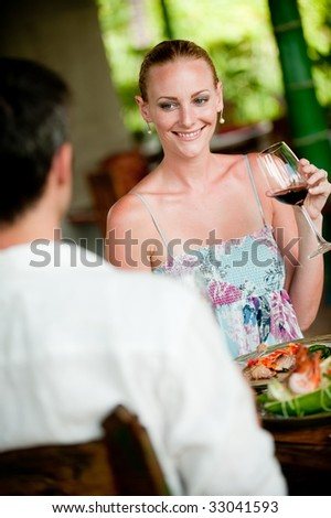A beautiful woman drinking wine whilst having meal with her male partner - stock photo