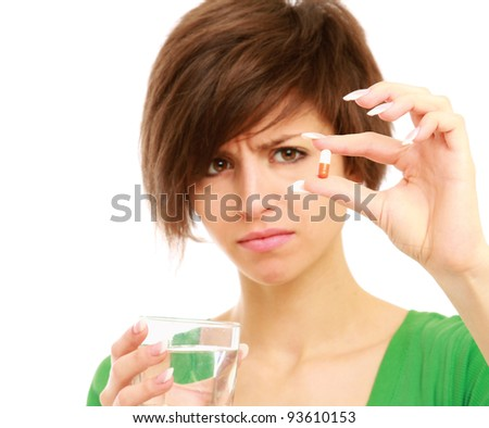 A beautiful woman holding a pill and water, isolated on white background - stock photo