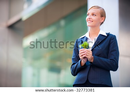 A beautiful woman holding a plant to signify business growth - stock photo