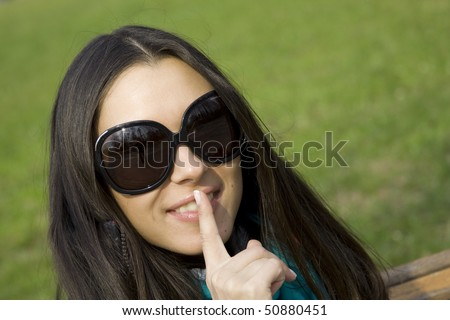 A beautiful woman holds a finger to his lips in token of silence. Portrait. Park - stock photo