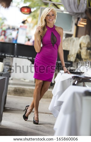 A beautiful woman in a cocktail dress at a local restaurant - stock photo