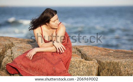 A beautiful woman in a red dress sits on a large rock at a beach during sunset. - stock photo