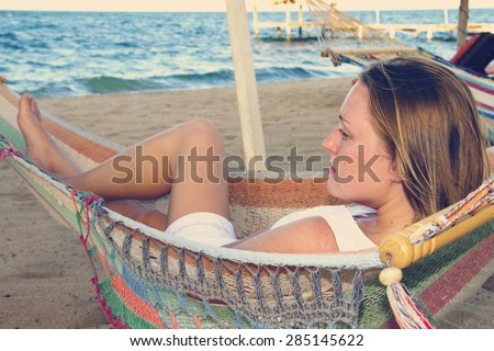 A beautiful woman in a white dress relaxing in a hammock - stock photo
