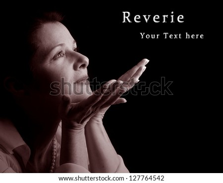 A beautiful woman in spiritual reverie, sepia with sample text - stock photo