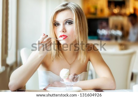 A beautiful woman in the restaurant is eating ice cream - stock photo