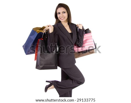 A beautiful woman is holding a lot of shopping bags and lifting one leg