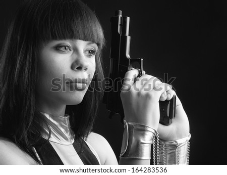 A beautiful woman is holding a pistol both hands on the dark background. She has a otherworldly look. She is manacled. Her hands are put into fetters with chains. - stock photo