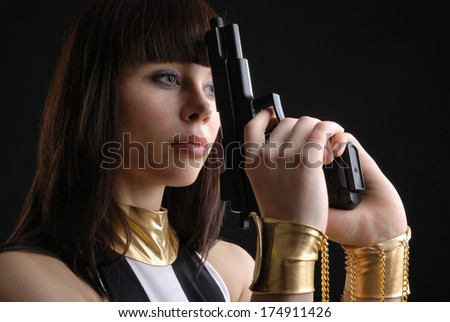 A beautiful woman is holding a pistol both hands on the dark background. She is manacled. Her hands are put into fetters with chains. - stock photo