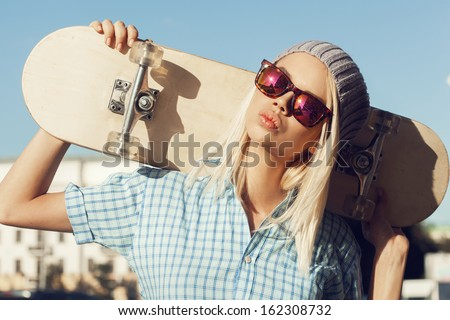 A beautiful woman is standing on the street and holding skateboard behind her head. The girl in joyful feelings. Outdoors, lifestyle. - stock photo