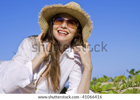 A beautiful woman lying smiling on the beach wearing hat and sunglasses - stock photo
