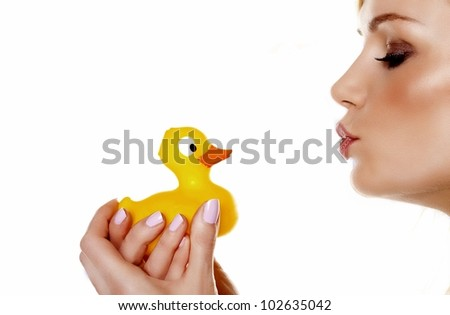 A beautiful woman pouting her lips to kiss her toy rubber duck. I love my ducky. - stock photo