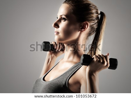 A beautiful woman raises with dumbbells - stock photo