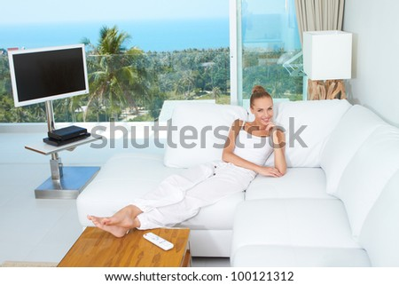 A beautiful woman relaxes on a white sofa in a modern airy bright living-room enjoying the luxury of a tropical lifestyle - stock photo