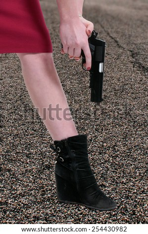 A beautiful woman shooting herself in the foot. - stock photo