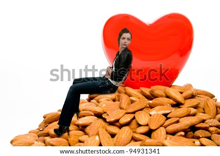 A beautiful woman sitting by a heart surrounded by cholesterol busting almonds - stock photo