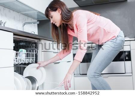 A beautiful woman using a dishwasher in a modern kitchen. domestic appliance - stock photo