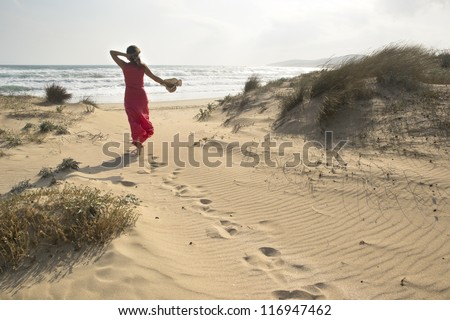 A beautiful woman walks through sand dunes towards to sea - stock photo