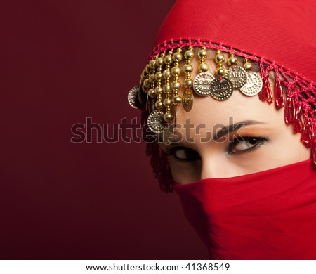 a beautiful woman wearing a red exotic veil - stock photo