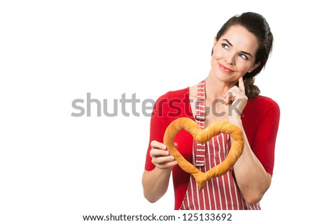 A beautiful woman wearing an apron smiling and holding a love heart made out of bread. Thinking and looking at copyspace.  Isolated on white.