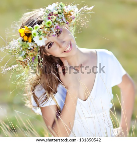 A beautiful woman with a wreath of flowers. - stock photo