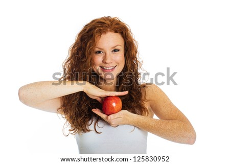 A beautiful woman with cute freckles holding an apple. - stock photo