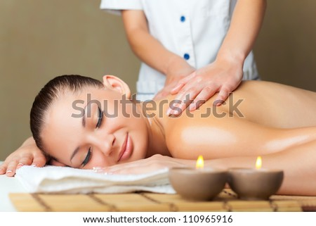 A beautiful woman with her �¢??�¢??eyes closed getting a massage at the spa - stock photo