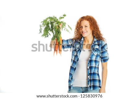 A beautiful woman with red hair holding farm fresh carrots - stock photo