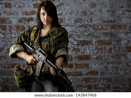 A beautiful yong soldier stands ready to fight for her rights. - stock photo