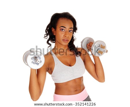 A beautiful young African American woman in a gray sports bra exercising with dumbbell's, isolated for white background. - stock photo