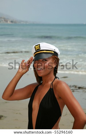 a beautiful young african american woman wears a sea captains hat while enjoying a day at the beach - stock photo
