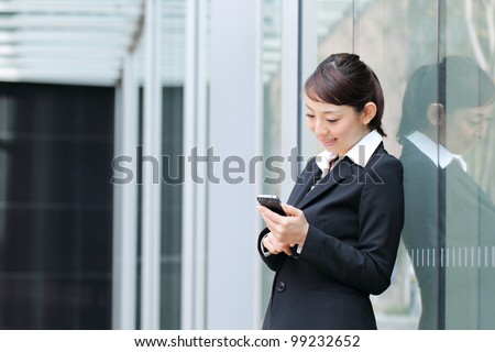 A beautiful young asian business woman on the cell phone at office