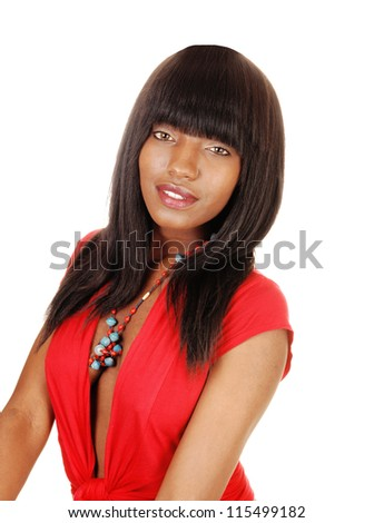A beautiful young black woman in a red blouse and long black hair sitting for white background and looking into the camera.