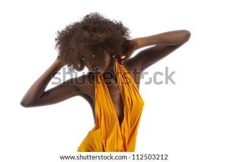 A beautiful young black woman places her hands behind her head creating angles with her body. - stock photo